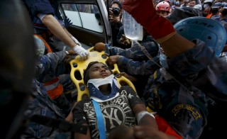 Earthquake survivor Pema Lama is rescued by the Armed Police Force from the collapsed Hilton Hotel, the result of an earthquake in Kathmandu