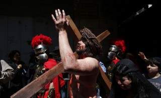 A man playing the role of Jesus carries a cross to the Church of the Holy Sepulchre in Jerusalem