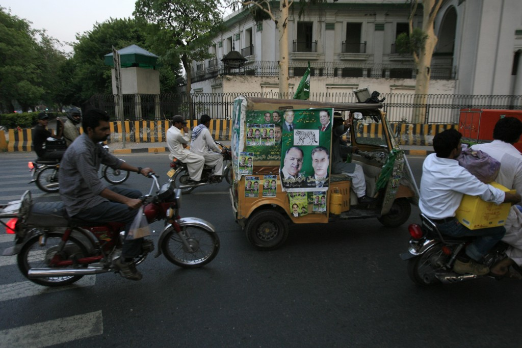 A man rides an auto rickshaw displaying election campaign posters in Lahore on May 6, 2013. Rickshaws are a popular form of transportation in Pakistan. Photo by Mani Rana/Reuters