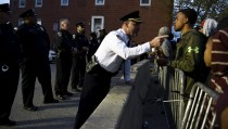 Captain Erik Pecha of the Baltimore Police Department chats with a young demonstrator in front of the Baltimore Police Department Western District station during a protest against the death in police custody of Freddie Gray in Baltimore on April 23, 2015. Photo by Sait Serkan Gurbuz/Reuters