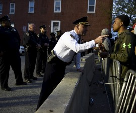 Captain Erik Pecha of the Baltimore Police Department chats with a young demonstrator during a protest against the death in police custody of Freddie Gray in Baltimore