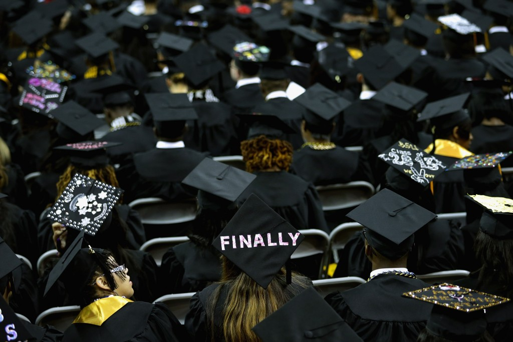 COLLEGE PARK, MD - MAY 17: Graduates of Bowie State University put messages on their mortarboard hats during the school's graduation ceremony at the Comcast Center on the campus of the University of Maryland May 17, 2013 in College Park, Maryland. First lady Michelle Obama delivered the commencement speech for the 600 graduates of Maryland's oldest historically black university and one of the ten oldest in the country. (Photo by Chip Somodevilla/Getty Images)