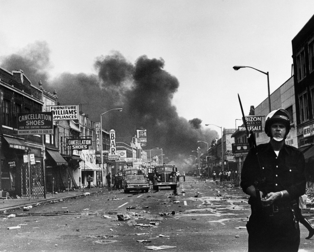 A policeman stands guard in a Detroit street on July 25, 1967 as buildings are burning during riots that erupted in Detroit following a police operation. Photo: AFP/Getty Images