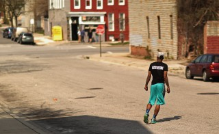 BALTIMORE, MD - APRIL 21:  A young man wears a shirt with the message 'Justice For Freddie' in the Sandtown neighborhood where he lives April 21, 2015 in Baltimore, Maryland. Gray was a 25-year-old black man who lived in this neighborhood and was arrested for possessing a switch blade knife April 12 outside the Gilmor Homes housing project on Baltimore's west side. According to his attorney, Gray died a week later in the hospital from a severe spinal cord injury he received while in police custody.  (Photo by Chip Somodevilla/Getty Images)