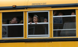 Children riding home from school on a school bus watch as Baltimore residents celebrate at the corner of West North Avenue and Pennsylvania Avenue after Baltimore authorities released a report on the death of Freddie Gray on May 1, 2015 in Baltimore. Photo by Win McNamee/Getty Images