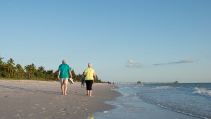 A couple walks along the Naples beach in Naples, Florida during the sunset on May 6, 2015. Photo by Ariel Min/PBS NewSHour
