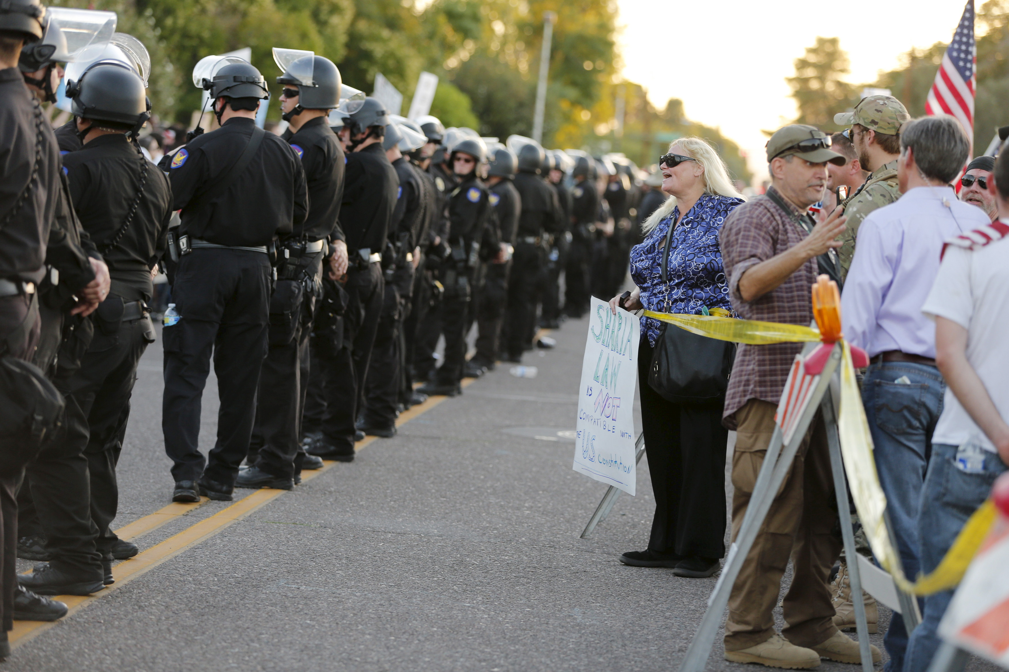 "A police line separates people attending the ""Freedom of Speech Rally Round II"" from counter demonstrators outside the Islamic Community Center of Phoenix. Police were on high alert because of a shooting at an anti-Muslim event in Texas in early May. Photo by Nancy Wiechec/Reuters."