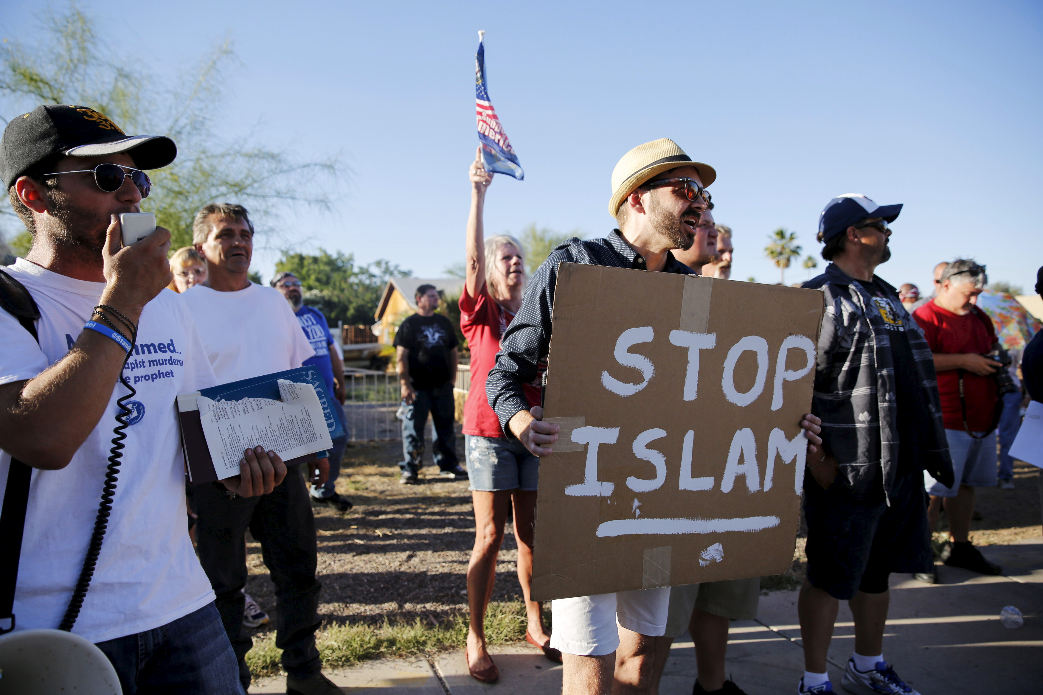 "A demonstrator shouts and carries a ""Stop Islam"" sign while another rips pages out of a Quran during a ""Freedom of Speech Rally Round II"" outside the Islamic Community Center of Phoenix, Arizona on May 29, 2015. Photo by Nancy Wiechec/Reuters."