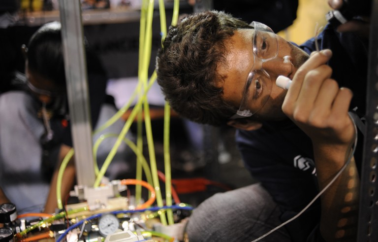 (JS) ROBOTICS27-- Angel Cruz, 16, of Lincoln High School works on his team robot during the FIRST Robotics competition at the University of Denver. The high school teams are guided by coaches and professional mentors who volunteer their expertise in accor