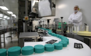 An employee of Teva Pharmaceutical Industries watches pill bottles on a conveyor belt at the company's Jerusalem oral solid dosage plant (OSD) December 21, 2011. Israel-based Teva is the world's leading generic drugmaker. Photo by Ronen Zvulun/Reuters