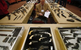 Antique gun collector Dave Kleiner reviews paperwork during the East Coast Fine Arms Show in Stamford, Connecticut, January 5, 2013. The show is being held despite the mayor's plea that the event not be held so soon after last month's massacre at an elementary school in nearby Newtown. Photo by Carlo Allegri/Reuters