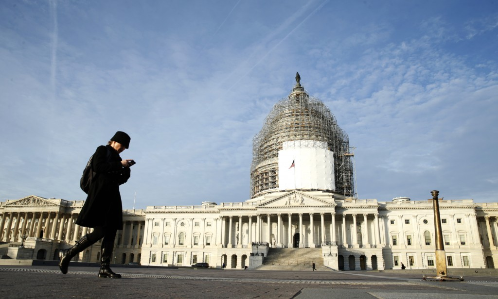 A woman checks her smartphone as she walks past the U.S. Capitol in Washington December 4,  2014.  U.S. President Barack Obama voiced optimism on Wednesday that a government shutdown can be avoided in coming weeks, pointing to comments from Republican leaders of Congress who oppose a budget showdown. Photo by Kevin Lamarque/Reuters