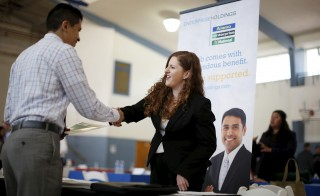 Jessica Kolber (R) shakes hands with a job seeker at a job fair in Burbank, Los Angeles, California March 19, 2015. The number of Americans filing new claims for unemployment benefits rose marginally last week, indicating the labor market remained on solid footing despite slowing economic growth. Photo by Lucy Nicholson/Reuters