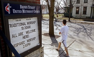 "A pedestrian walks past a sign reading ""All are Welcome"" at Brown Street United Methodist Church in downtown in Lafayette, Indiana March 31, 2015. Indiana's Republican Governor Mike Pence, responding to national outrage over the state's new Religious Freedom Restoration Act, said on Tuesday he will ""fix"" it to make clear businesses cannot use the law to deny services to same-sex couples. Photo by Nate Chute/Reuters"