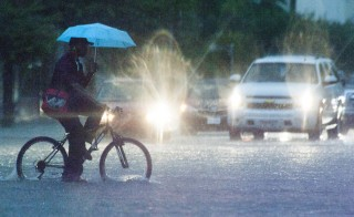 A man bikes through a heavily flooded road in downtown Houston, Texas May 30, 2015. Photo by Lee Celano/Reuters