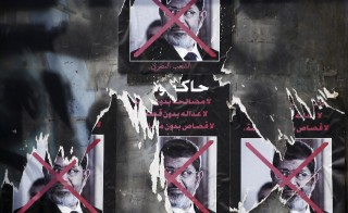 "Torn posters of ousted Egyptian President Mohamed Morsi  that read, ""To be on trial... No reconciliation without justice, no justice without retribution, no punishment without trial"" are seen in Tahrir Square in Cairo September 26, 2013. Morsi was senteced to death by an Egyptian court Saturday. Photo by Amr Abdallah Dalsh/Reuters"