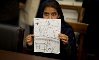 Nabila Rehman, 9, holds up a picture she drew depicting the U.S. drone strike on her Pakistan village which killed her grandmother Mammana Bibi, at a news conference on Capitol Hill in Washington October 29, 2013. Nabila and her father and brother attended the news conference to highlight the personal costs in collateral damage for civilians killed and injured in the U.S. drone strike program. Photo by Jason Reed/Reuters