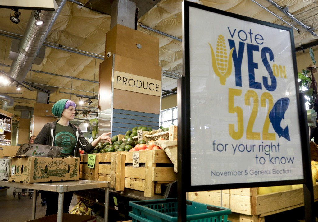 An employee stocks produce near a sign supporting a ballot initiative in Washington state that would require labeling of foods containing genetically modified crops at the Central Co-op in Seattle, Washington October 29, 2013. Major U.S. food and chemical companies are pouring millions of dollars into efforts to block approval of the initiative. Photo by Jason Redmond/Reuters