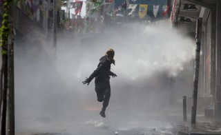 A masked protester runs away from a water cannon's jet during clashes with police in Okmeydani neighbourhood in Istanbul, Turkey, May 1, 2015. Istanbul went into a security lockdown on Friday as thousands of police manned barricades and closed streets to stop May Day rallies at Taksim Square, a symbolic point for protests. REUTERS/Kemal Aslan