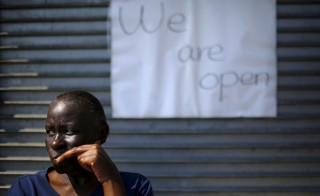 Local resident stands in front of a reopened store at the corner of North Avenue and Pennsylvania Avenue in Baltimore