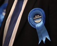 A Conservative party supporter wears a rosette in support of Prime Minister and local member of Parliament David Cameron at the counting centre, as votes are counted in Britain's general election, in Witney