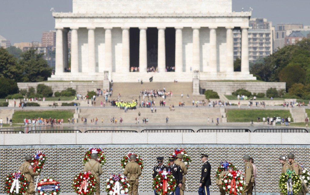 Soldiers dressed in WWII uniforms place wreaths in front of the Freedom Wall, with the Lincoln Memorial in the background, at the World War II Memorial during a ceremony to commemorate the 70th anniversary of VE (Victory in Europe) Day in Washington May 8, 2015. Photo by Kevin Lamarque/Reuters