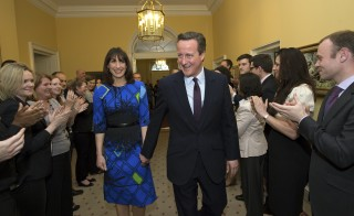 Workers applaud as Britain's Prime Minister David Cameron and his wife Samantha return to Number 10 Downing Street in London