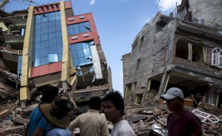 People walk past a collapsed building after a fresh 7.3 earthquake struck, in Kathmandu