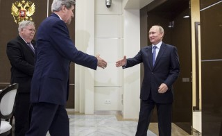 U.S. Secretary of State John Kerry (C) shakes hands with Russian President Vladimir Putin as U.S. Ambassador to Russia John Tefft (L) watches at the presidential residence of Bocharov Ruchey