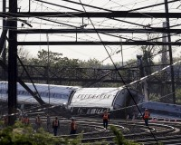 Officials survey the site of a derailed Amtrak train in Philadelphia Wednesday morning. The accident left rail cars mangled, ripped open and strewn upside down in the city's Port Richmond neighborhood along the Delaware River. Photo by Mike Segar/Reuters