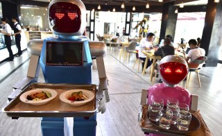 Robot couple Xiaolan (L) and Xiaotao carry trays of food at a restaurant in Jinhua, Zhejiang province, China, May 18, 2015. The restaurant, which opened on Monday has two robots delivering food for customers. The robots were designed as a couple, Xiaolan and Xiaotao, according to local media. Photo by Reuters