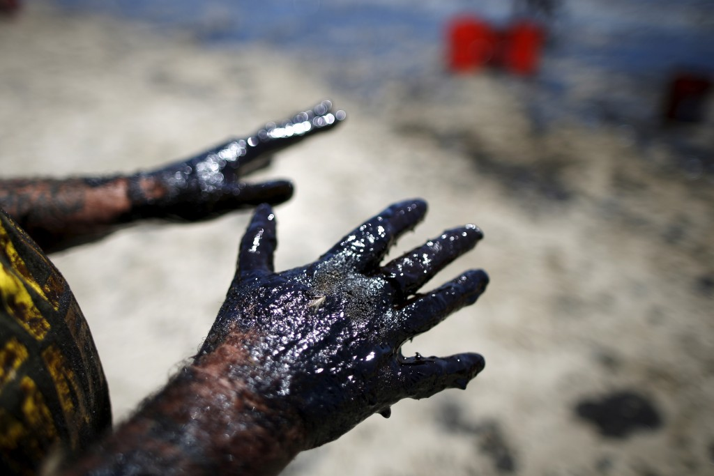 Volunteer William McConnaughey, 56, who drove from San Diego to help shovel oil off the beach, stretches out his hands after carrying buckets of oil from an oil slick along the coast of Refugio State Beach in Goleta, California, United States, May 20, 2015. Photo by Lucy Nicholson/Reuters