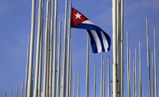 The Cuban flag flies in front of the U.S. Interests Section (background), in Havana May 22, 2015.  Photo by Enrique de la Osa/Reuters