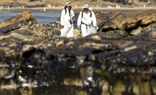 Crew members inspect the oil spill damage at Refugio State Beach in Goleta, California May 22, 2015. As much as 2,500 barrels (105,000 gallons) of crude oil, according to latest estimates, gushed onto San Refugio State Beach and into the Pacific west of Santa Barbara when an underground pipeline running parallel to a coastal highway there inexplicably burst on Tuesday morning. REUTERS/Jonathan Alcorn - RTX1E6KQ