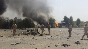Iraqi security forces inspect the site of a car bomb attack on the outskirt of Diyala province