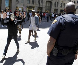 Protester with his hands up walks by a Cleveland police officer following a not guilty verdict for Cleveland police officer Michael Brelo on manslaughter charges, in Cleveland, Ohio