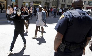 A protester with his hands up walks by a Cleveland police officer following a not guilty verdict for Cleveland police officer Michael Brelo on manslaughter charges, in Cleveland, Ohio, May 23, 2015.  Photo by U.S.  REUTERS/Aaron Josefczyk