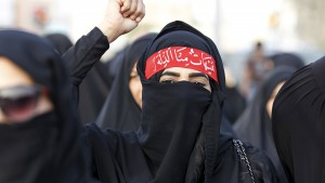 A protester shout pro-Shi'ite slogans as she march in the village of Sanabis west of Manama, Bahrain, to show solidarity for victims of a suicide bomb attack in Saudi Arabia