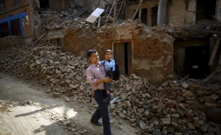 Birendra Karmacharya carries his son Saksham Karmacharya, 4, as they walk past the debris of collapsed houses while heading toward school in Bhaktapur, Nepal on May 31, 2015. Photo by Navesh Chitrakar/Reuters
