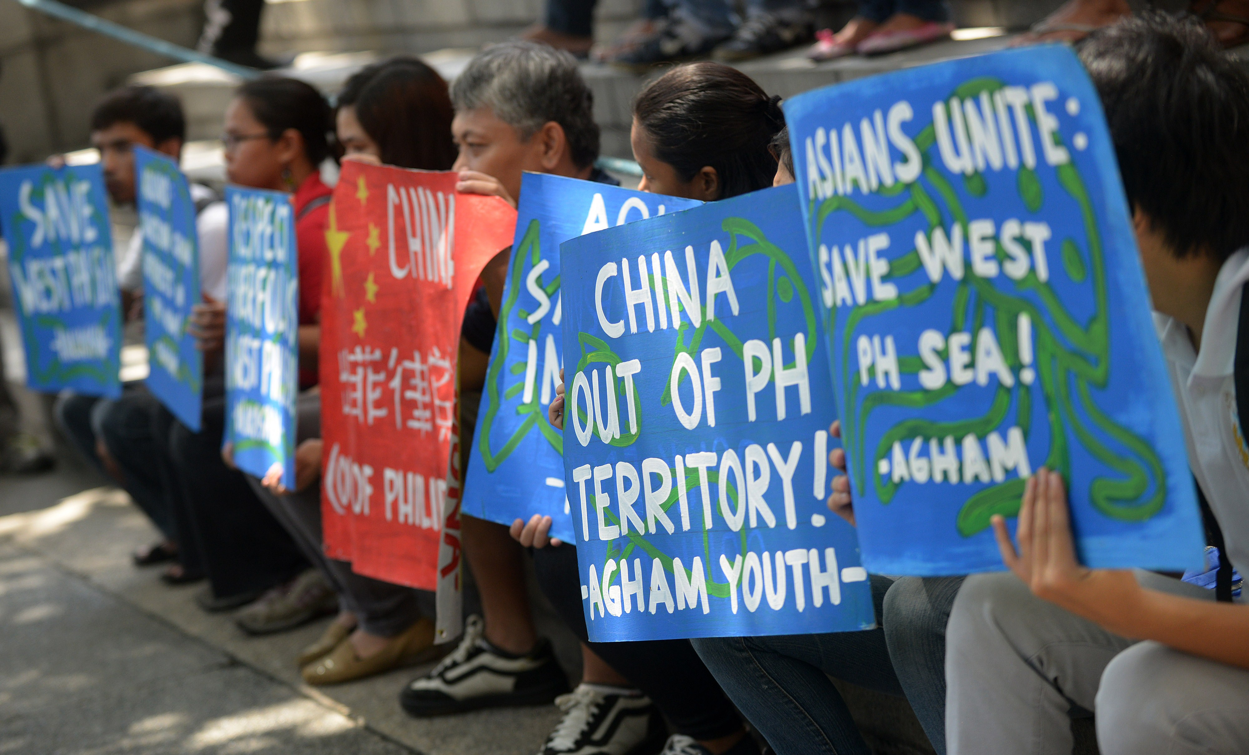 Filipino environmental activists display placards during a rally outside China's consular office in Manila on May 11, 2015, against China's reclamation and construction activities on islands and reefs in the Spratly Group of the South China Sea that are also claimed by the Philippines. Photo by JAY DIRECTO/AFP/Getty Images.