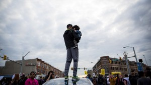 A man holds a child on a car at North Ave and Pennsylvania Ave in Baltimore, Maryland
