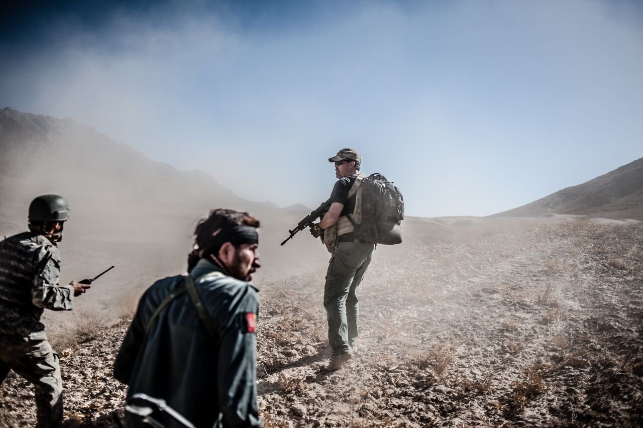 Terry Arsenault, a private military contractor with Tundra Group, leads Afghan police officers to the site of a bomb strike that killed a young woman near Combat Outpost Mizan in Zabul. Photo by Ben Brody/The GroundTruth Project
