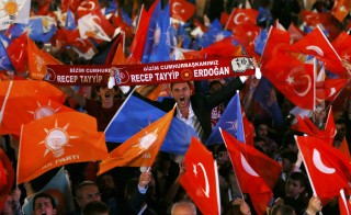 Supporters wave Turkish national and party flags outside the AK Party headquarters in Ankara, Turkey, June 7, 2015. Turkish President Tayyip Erdogan's hopes of assuming greater powers suffered a serious blow on Sunday when the ruling AK Party failed to win an outright majority in a parliamentary election, partial results showed. With 94 percent of ballots counted, the AKP had taken 41 percent of the vote, according to broadcaster CNN Turk, a result which will leave it struggling to form a stable government for the first time since it came to power more than a decade ago. REUTERS/Umit Bektas TPX IMAGES OF THE DAY