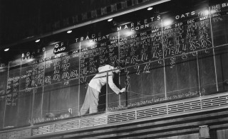 A man updates the chalkboard at the Chicago Board of Trade in Chicago, Illinois in this undated handout photo. July 6 will mark the end of more than eight decades of open-outcry grain futures trading at the landmark Chicago Board of Trade Building. Image courtesy of Chicago History Museum, Gordon H. Coster via Reuters