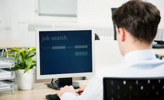 Office worker using computer to perform job search