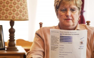 Senior woman reading Social Security form. Photo by Getty Images