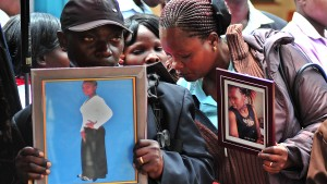 Relatives hold portraits of those killed, as they wait to retrieve their bodies, at the Chiromo funeral parlor on April 9, 2015 in Nairobi. 148 people, mainly students, were killed during a dawn raid by Islamist-gunmen in an attack claimed by Somalia-based al-Shabab a week ago on the northeastern Kenyan Garissa University campus. The Kenyan government has started to release the bodies to their families. AFP PHOTO/STRINGER        (Photo credit should read -/AFP/Getty Images)