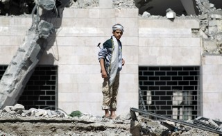 A Huthi Shiite militant inspects what remains of a hotel destroyed in an air-strike by the Saudi-led coalition on May 31, 2015 in Al-Thawra sport city located north of the capital Sanaa. Human Rights Watch published new evidence alleging a Saudi-led coalition is using internationally banned cluster bombs in Yemen, urging it to stop such attacks that were harming civilians.     AFP PHOTO / MOHAMMED HUWAIS        (Photo credit should read MOHAMMED HUWAIS/AFP/Getty Images)