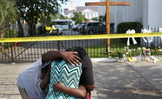 CHARLESTON, SC - JUNE 19: People mourn together in front of the Emanuel African Methodist Episcopal Church after a mass shooting at the church that killed nine people of June 19, 2015. A 21-year-old white gunman is suspected of killing nine people during a prayer meeting in the church, which is one of the nation's oldest black churches in Charleston. (Photo by Joe Raedle/Getty Images)