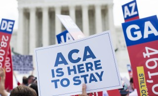 Affordable Care Act supporters wave signs outside the Supreme Court after the court ruled on the future of health care subsidies Thursday. Photo By Bill Clark/CQ Roll Call